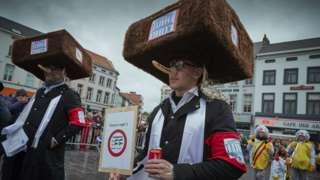 На карнавале появились люди в огромных меховых шапках и с приставными носами - видимо, это карикатурное изображение евреев-ортодоксов
