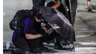 Manifestantes tentam se proteger de balas de borracha e gás lacrimogênio em Kenosha, Washington
