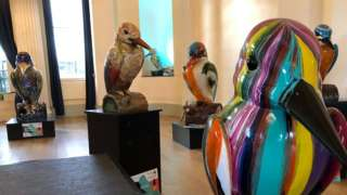 Several of the colourful kingfisher sculptures on display in the auction house