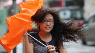台风韦森特迫近香港之际一位女士持伞狼狈走过街头(23/7/2012)