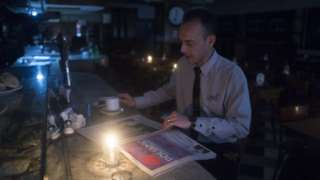 A man reads a newspaper by candlelight during the blackout in Argentina