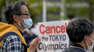 A protester carries a placard during a demonstration against the Tokyo Olympics in front of the New National Stadium, the main stadium for the Tokyo Olympics.