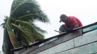 A man prepares his roof as a powerful hurricane approaches