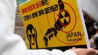 首尔日本驻韩国大使馆外一名示威者手持抗议日本排放福岛核电站废水的标语牌(13/4/2021)