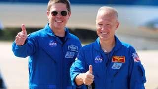 Bob Behnken e Doug Hurley, de jalecos da Nasa, pousam para foto sorrindo