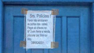 Imagem mostra porta azul de casa com aviso que diz: 'srs. policias! Favor não arrombarem as portas das casas, pegar as chaves no no. 3 em frente à avenida, procurar por (ilegível) ou (ilegível), obrigado!'