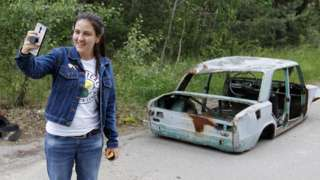 A visitor posses for a selfie next to a wrecked car at the Chernobyl exclusion zone