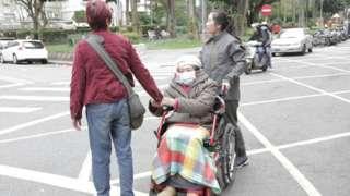 Muji wheels Ana's wheelchair across the road.