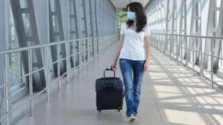 Mujer con mascarilla y valija