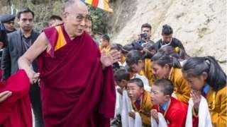 "A handout photo made available by Tenzin Choejor, the Dalai Lama""s Office shows followers greet Tibetan spiritual leader,"