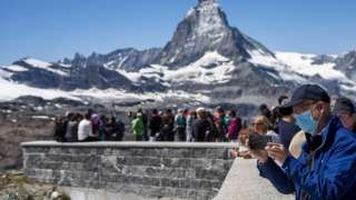 Tourist wearing a protective face mask takes a picture in front of the Matterhorn