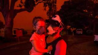 Mike hold his daughter Ella as the skies above turn red during the day on January 4, 2020 in Mallacoota, Australia