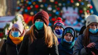 """Russian people wearing a protective face masks walk on a street decorated for the upcoming Christmas and New Year""""s celebrations during the pandemic of SARS-CoV-2 coronavirus Moscow, Russia, 28 December 2020"""