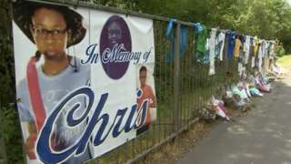 Flower tributes and banners near to where Christopher died