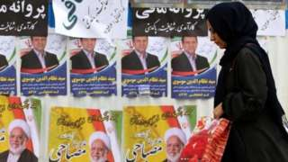 Iranian woman walks past election campaign posters in Tehran (19/02/20)