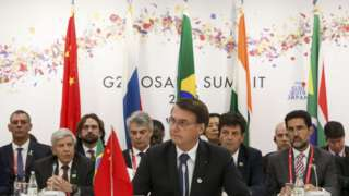 Bolsonaro discursa e assessores e bandeiras aparecem ao fundo