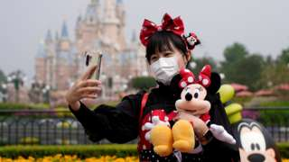 A visitor dressed as a Disney character takes a selfie while wearing a protective face mask at Shanghai Disney Resort as the Shanghai Disneyland theme park reopens following a shutdown due to the coronavirus disease (COVID-19) outbreak, in