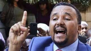 Jawar Mohammed (C), membre du groupe ethnique Oromo qui a critiqué publiquement Abiy, s'adresse aux partisans qui s'étaient rassemblés devant son domicile dans la capitale éthiopienne, Addis-Abeba, après qu'il ait accusé les forces de sécurité d'avoir tenté d'orchestrer une attaque contre lui le 24 octobre 2019