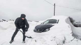 A man digs out a car stuck in snow in Ripponden, Yorkshire