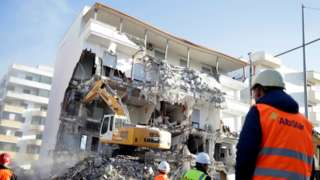 A bulldozer works at a collapsed building in Durres