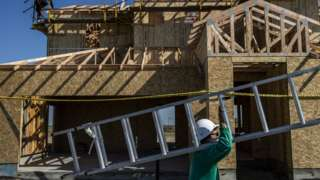 A worker carries a ladder into a home under construction at the planned community at River Islands in Lathrop, California Thursday, Mar. 4, 2021.