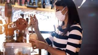 A woman pulling a pint wearing a mask