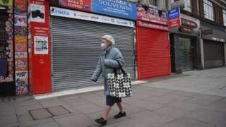 A woman walking down an empty street in London