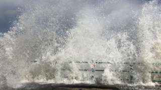 Water breaking over pier
