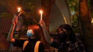 Dos mujeres levantan velas en el parque Victoria de Hong Kong.