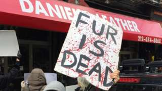 Man holding 'fur is dead' protest sign