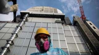 Tepco employee in front of the reactor three at Fukushima Daiichi nuclear power plant in Okuma, Fukushima prefecture, 31 Jan 2018