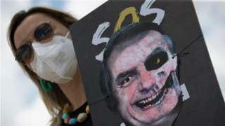 A woman holds a poster with an image representing the President of Brazil, Jair Bolsonaro, painted as a skull, during a demonstration rejecting the handling of the pandemic by his Government, in Brasilia, Brazil, 20 October 2021.