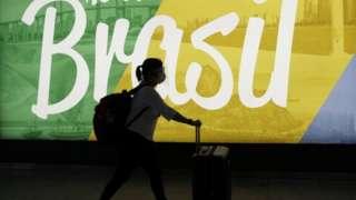 Mulher caminha com mala em frente a propaganda do Brasil