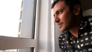 Dr Sanjay Gupta looking out a hotel window