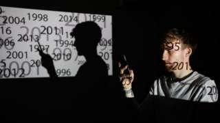 Човек држи мобилни телефон у мраку