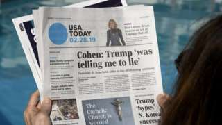A woman reading USA Today
