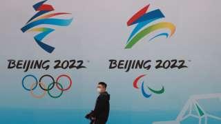 北京水立方一位途人走过2022年北京冬奥会与冬残奥会标志(9/4/2021)