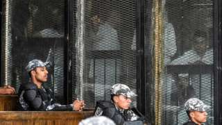"""Members of Egypt""""s banned Muslim Brotherhood are seen inside a glass dock during their trial in the capital Cairo on July 28, 2018."""