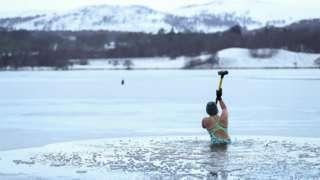 Alice Goodridge breaks the ice at Loch Insh, Scotland, 30 December 2020.