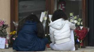 Youngsters look at floral tributes laid at the school in Conflans Saint-Honorine where the murdered teacher was from, on 17 October 2020
