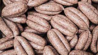 High angle close up of freshly made pork sausages at a butcher shop