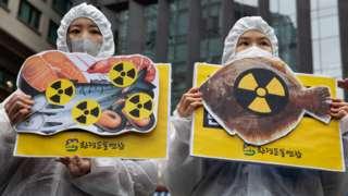 韓國環保活動人士在首爾日本大使館外舉起象徵海鮮受核輻射污染的抗議標語牌(13/4/2021)