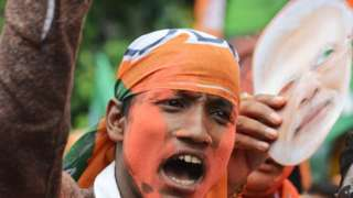 An Indian supporter of Bharatiya Janata Party (BJP) celebrates the party's win in the general election.