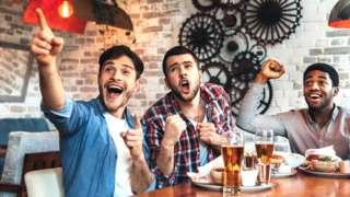 Cheering on their team - friends in a bar