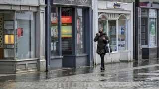 Woman walking past shops in Bridgend