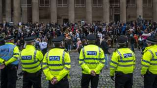 police officers watch demonstrators