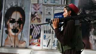 A Taliban fighter walks past a beauty salon with images of women defaced using spray paint in Shar-e-Naw in Kabul on August 18, 2021.