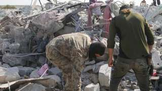 Two men stand amid rubble at scene of building destroyed by US after killing of Abu Bakr al-Baghdadi in Idlib province (27/10/19)