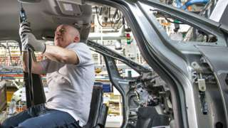 Stock image of a worker in a car factory