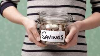 Woman holding savings jar